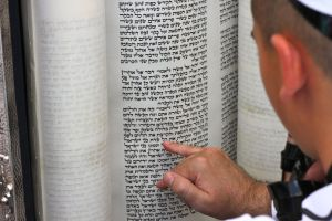 A boy reads the ancient Hebrew text from a Torah scroll at his Bar Mitzvah at the Western Wall holy site in Jerusalem. (Photo: Daniel Estrin)